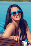 Portrait of smiling young woman laying on sunbed Royalty Free Stock Photo