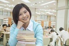 Portrait of Smiling Young Woman in Library Royalty Free Stock Images