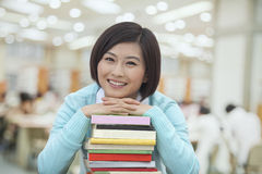 Portrait of Smiling Young Woman in Library Leaning on a Stack of  Books, Looking At Camera Stock Photography