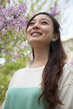 Portrait of smiling young woman with long hair outdoors in the park in springtime Stock Photos