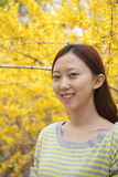 Portrait of smiling young woman with long hair outdoors in the park in springtime with yellow blossoms Royalty Free Stock Photo