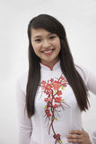 Portrait of smiling young woman with long hair wearing a traditional dress from Vietnam, studio shot Royalty Free Stock Photos
