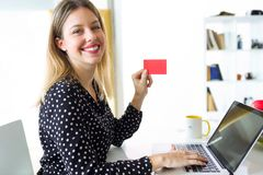 Smiling young woman looking at camera while holding red credit card for shopping online with computer at home stock photos