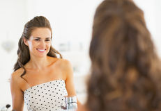 Portrait of smiling young woman looking in mirror Stock Photos