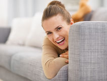 Portrait of smiling young woman looking out from divan. In living room Stock Photos