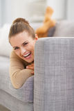 Portrait of smiling young woman looking out from sofa Royalty Free Stock Images