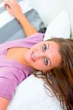 Portrait of smiling young woman lying on couch Stock Photos