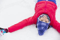 Portrait of smiling young woman lying on snow Royalty Free Stock Images