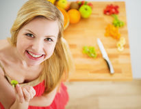Portrait of smiling young woman making fruits salad. In modern kitchen royalty free stock photography
