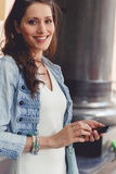 Portrait of smiling young woman with mobile phone Royalty Free Stock Images