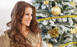 Portrait of smiling young woman near christmas tree. Looking on copy space Royalty Free Stock Photography