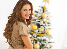 Portrait of smiling young woman near christmas tree. In room Stock Photo