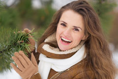Portrait of smiling young woman near fir-tree. In winter park Stock Photo