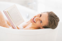 Portrait of smiling young woman reading book in bathtub Royalty Free Stock Image