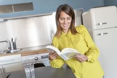 Portrait of smiling young woman reading book in kitchen at home Stock Photo