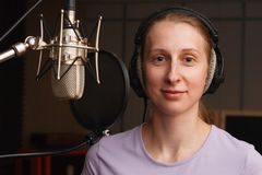 Portrait of a smiling young woman in the recording studio with microphone stock images
