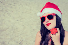 Portrait of a smiling young woman  in Santa Claus hat and sungla Royalty Free Stock Image