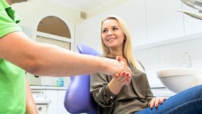 Portrait of smiling young woman shaking hands with dentist in his office. Smiling young women shaking hands with dentist in his office Royalty Free Stock Photos