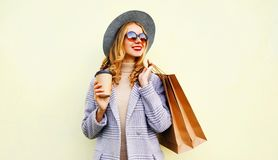 Portrait smiling young woman with shopping bags, holding coffee cup, wearing pink coat, round hat on background. Portrait smiling young woman with shopping bags stock images