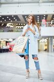 Modern Young Woman Shopping on Black Friday. Portrait of smiling young woman shopping on Black Friday holding smartphone and paper bags with purchases Stock Photography
