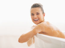 Portrait of smiling young woman sitting in bathtub Stock Photos