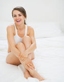 Portrait of smiling young woman sitting on bed Royalty Free Stock Photography