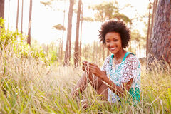 Portrait Of Smiling Young Woman Sitting In Countryside Royalty Free Stock Image