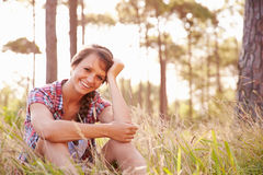 Portrait Of Smiling Young Woman Sitting In Countryside Royalty Free Stock Photography