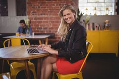 Portrait of smiling young woman sitting with laptop at coffee shop Stock Images
