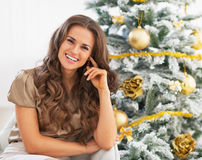 Portrait of smiling young woman sitting near christmas tree Royalty Free Stock Photos