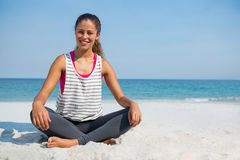 Portrait of smiling young woman sitting on sand at beach. Against clear blue sky Stock Image