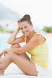 Portrait of smiling young woman sitting on sunbed Royalty Free Stock Photography