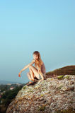 Portrait of a smiling young woman sitting on the top of mountain Royalty Free Stock Image