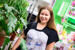 Portrait of smiling young woman standing with green plants Royalty Free Stock Photos