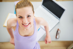 Portrait of smiling young woman studying in kitchen Royalty Free Stock Photo