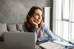Portrait of a smiling young woman studying. While sitting at the table with laptop computer and notebook at home Royalty Free Stock Photos