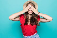 Portrait of a smiling young woman in summer hat covering eyes with her arms over blue background stock photos