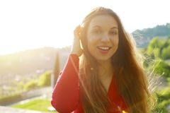 Portrait of smiling young woman with sunlight flare and copy space stock image
