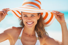 Portrait of smiling young woman in swimsuit and beach hat Royalty Free Stock Images