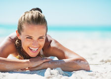 Portrait of smiling young woman in swimsuit laying on beach Stock Photos