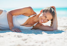 Portrait of smiling young woman in swimsuit laying on beach Stock Photo