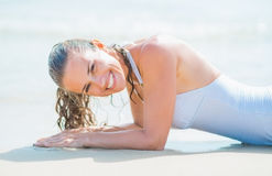 Portrait of smiling young woman in swimsuit laying on sea shore Stock Images