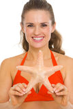 Portrait of smiling young woman in swimsuit showing starfish Royalty Free Stock Photography
