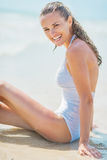 Portrait of smiling young woman in swimsuit sitting on sea coast Royalty Free Stock Image