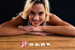 Portrait of woman by table with ribbon and care text Royalty Free Stock Photo
