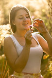 Portrait of smiling young woman tearing petal off flower at fiel Royalty Free Stock Photos