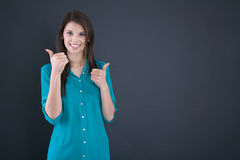Portrait of a smiling young woman with thumbs up in school. Portrait of a smiling young woman with thumbs up in school - passed examination stock photo