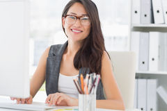 Portrait of a smiling young woman using computer Royalty Free Stock Image