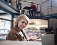Portrait of smiling young woman using tablet PC in cafe Royalty Free Stock Images