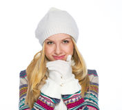 Portrait of smiling young woman in winter clothes warming hands Royalty Free Stock Photo
